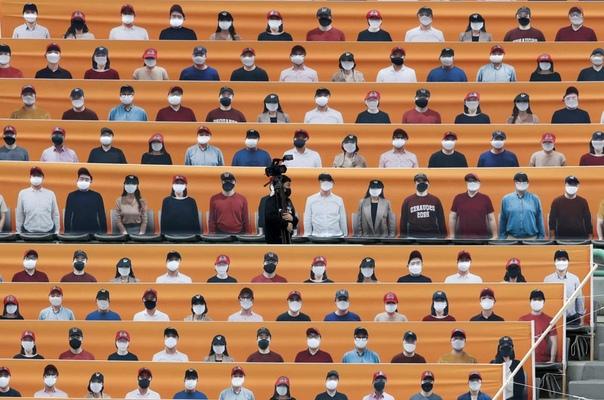Оператор проходит между рядами с баннерами, изображающими зрителей бейсбольного матча в Инчхоне. Профессиональная бейсбольная лига Южной Кореи начинает новый сезон без болельщиков.