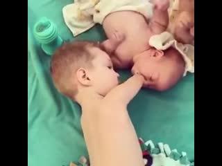 Брат помогает своей младшей сестре.