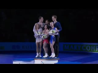 2nd & 3rd place winners of world figure skating championships help to lift the champion for podium photo